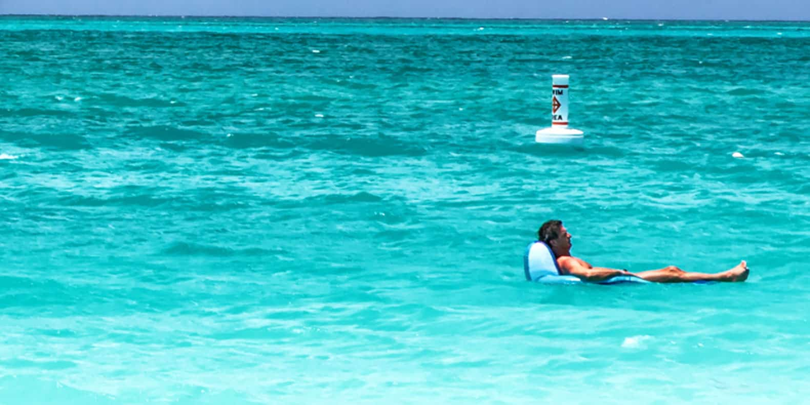 Photo of Billy McFarland floating on an inflatable recliner drifts in a turquoise blue ocean.